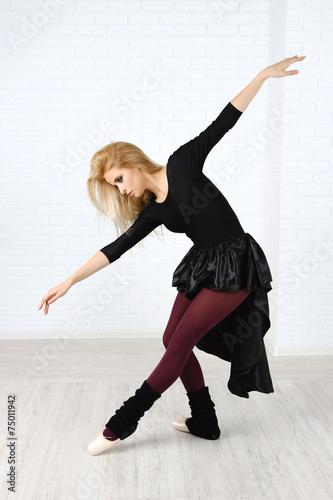 Plexiglas Beautiful young ballerina on wall background