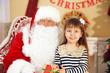 Santa Claus giving  present to  little cute girl near Christmas