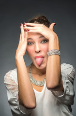 Young beautiful woman pokes out her tongue. Isolated on grey