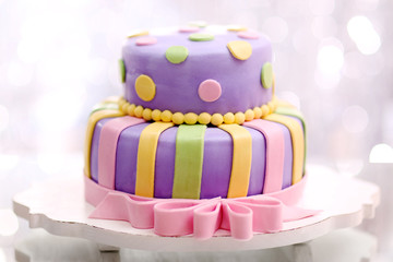 Delicious birthday cake on shiny silver background