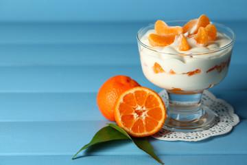Tasty milk dessert with fresh tangerine pieces in glass bowl,