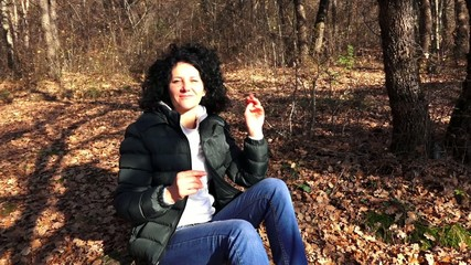 Woman relaxing in a forest after hiking