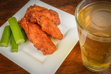 Chicken Buffalo Wings with Celery Sticks and Beer