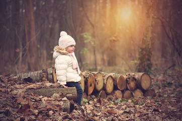 Little girl sit in the autumn forest