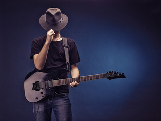 A musician with a guitar in a black hat on a dark background.