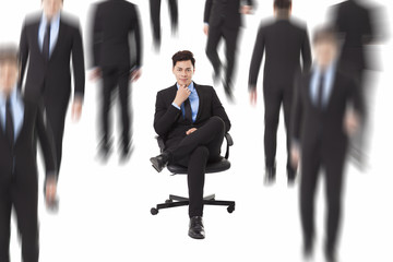Young businessman sitting in a chair and people walking through