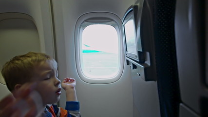 Little boy touching seat monitor in plane