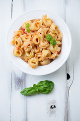 Glass plate with tortellini in tomato sauce, view from above