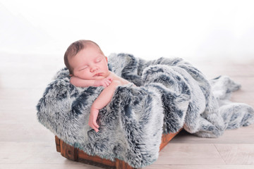 Newborn baby on a fur blanket