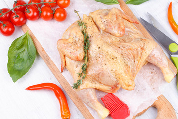 Fresh raw chicken prepared for roast with thyme and tomatoes
