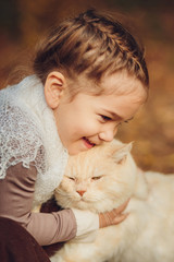 Cute girl with a cat in vintage clothes in autumn forest