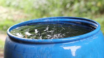 Rainwater harvesting to a blue barrel.