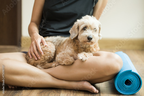 Tuinposter Gymnastiek woman holding dog in yoga class