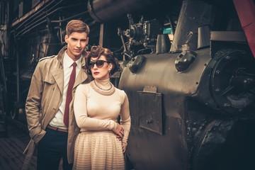 Vintage style couple near steam locomotive