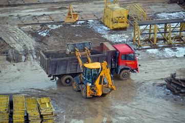Трактор нагружает грузовик на строительной площадке