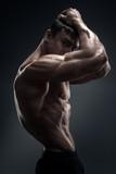 Fototapety Handsome muscular bodybuilder preparing for fitness training.