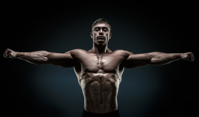 Handsome muscular bodybuilder posing and keeping arms outstretch