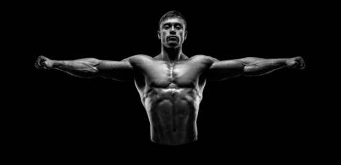 Bodybuilder posing and keeping arms outstretch black and white