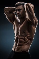 Handsome muscular bodybuilder posing over black background