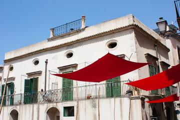 Façade maison en Sicile et toiles rouges