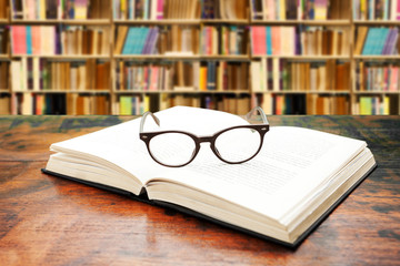 book and glasses against library background