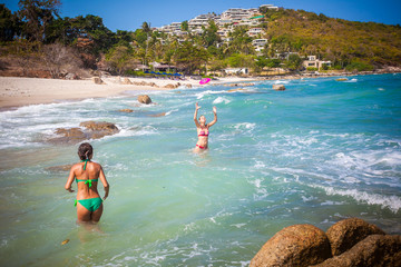beautiful young woman wearing a green bikini playing frisbee at