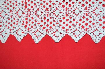 Белое кружево на фоне красной ткани