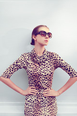 Fashion and people concept - pretty sexy woman in leopard dress