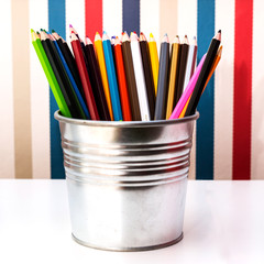 Colorful pencils in pails on vertical stripes background.