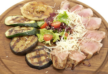 meat roasted on a grill with vegetables on a wooden plate