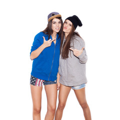 Two young stylish girlfriends in hoodies showing middle finger