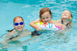 two little girls and little boy playing in the swimming pool