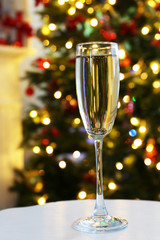 Champagne glass on table, on fir-tree background