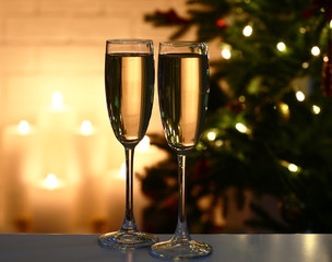 Champagne glasses on table, on fir-tree and fireplace