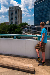 Man looking at buildings from the top of a parking garage in Tow