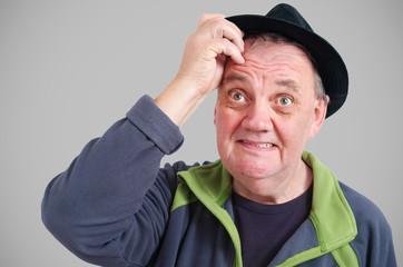 Homme avec chapeau qui réfléchi main a la tête
