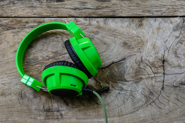 Green headphone on wooden table
