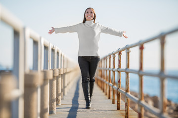 young woman with open arms walking, selective focus
