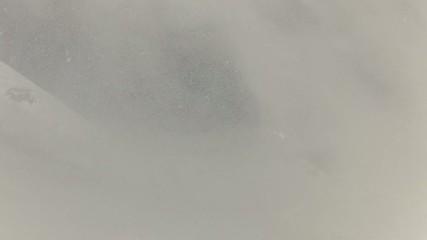 Skier descends slope, sprays powder snow into camera
