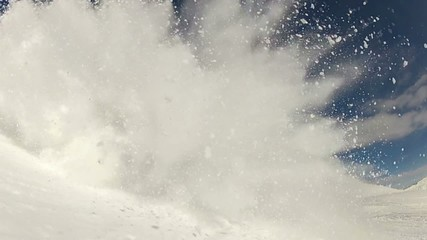 Skier carving and spraying snow at camera, slowmotion