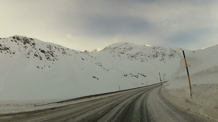 Point of view, car driving on mountain snowy road