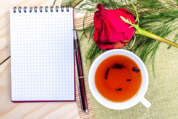 cup of tea with open notepad, top view