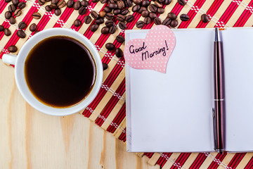 open notepad with cup of coffee on striped napkin