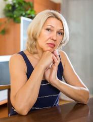 Sad mature  woman sitting near table