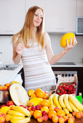 Positive blonde  woman with melon and   fruits