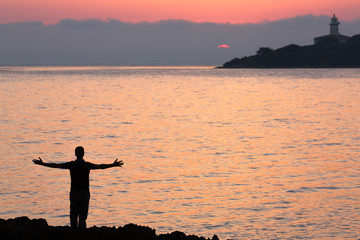 silhouette of young men with open arms looking to the sunrise