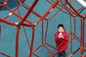 Boy with phone on the playground in the park