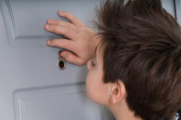 boy looking through the peephole