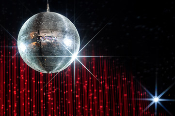 Disco ball with stars in nightclub lit by spotlight