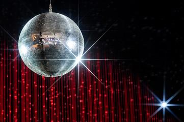 Disco ball with stars in nightclub lit by spotlight